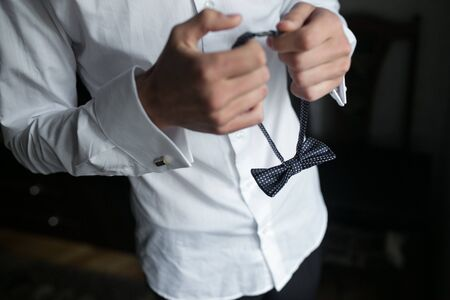 cuff link: close view of the groom who is preparing for the wedding