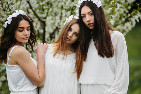 clambering: three beautiful girls posing in the garden at the camera Stock Photo