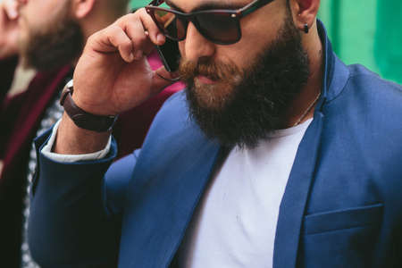 three day beard: two businessmen talking on the phone in the city