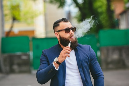 cigarette smoke: Stylish bearded man walks through the city