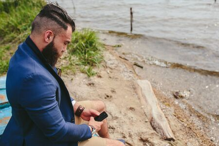 three day beard: American Bearded Man looks on the river bank in a blue jacket Stock Photo