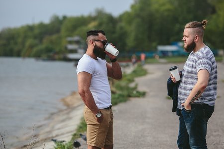 three day beard: Two men standing on the beach and drink coffee Stock Photo