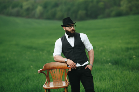 three day beard: a man with a beard is standing near the chair on the field Stock Photo