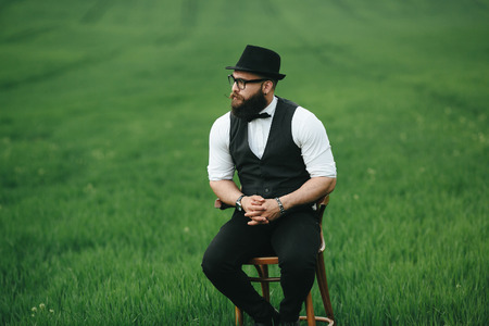 three day beard: a man with a beard sitting on a chair on the field
