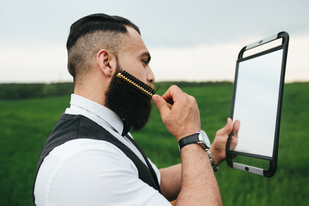 greem: a man with a beard looking at herself in the mirror on the nature