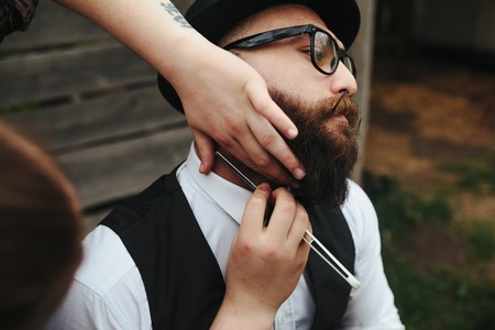 three day beard: barber shaves a bearded man in vintage atmosphere Stock Photo