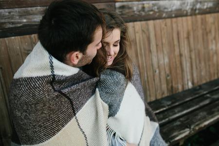 parejas jovenes: Joven pareja de enamorados envuelta en sesi�n de tela escocesa y divertirse