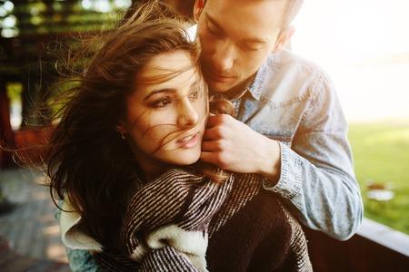 Jong paar in liefde verpakt in plaid staande en omarmen Stockfoto