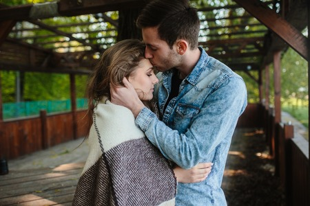 young couple hugging kissing: Young couple in love wrapped in plaid standing and kissing Stock Photo