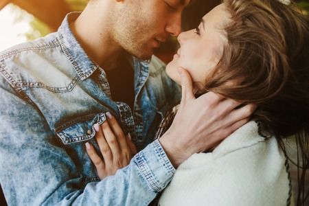 Young couple in love wrapped in plaid standing and looking at each other Stockfoto