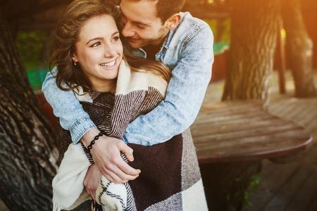 pareja abrazada: Pareja joven en el amor envuelto en tela escocesa de pie y abrazar Foto de archivo