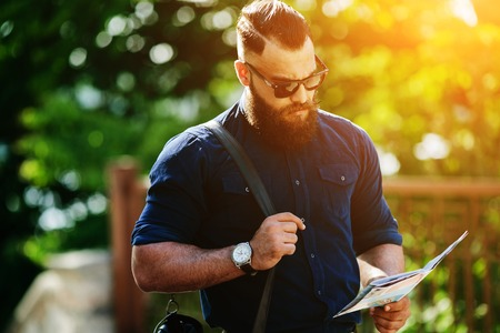 man in jeans: bearded man sitting and looking at a map Stock Photo