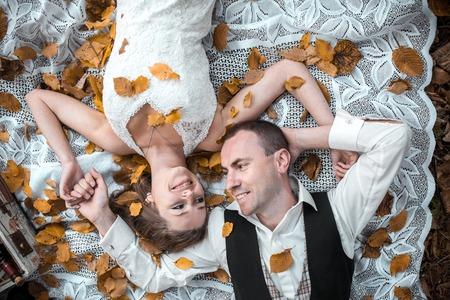 Beautiful wedding couple lying under a tree Banque d'images