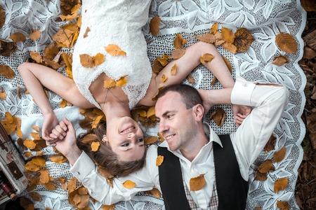 under a tree: Beautiful wedding couple lying under a tree Stock Photo