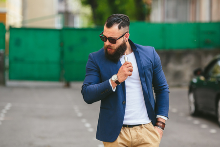 well dressed: well dressed man with a beard smoking electronic cigarette