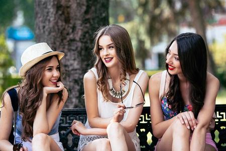 Tres chicas jóvenes hermosas que presentan contra el telón de fondo del parque Foto de archivo - 48026990