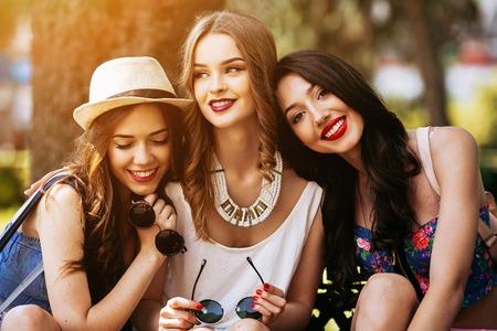 dívka: Tři krásné mladé dívky představující na pozadí parku Reklamní fotografie