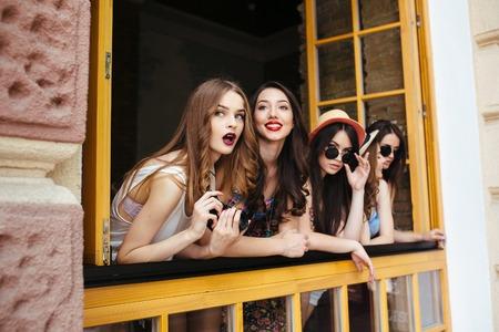 mujeres fashion: cuatro hermosas chicas j�venes miran hacia fuera de la ventana