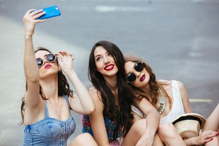 models posing: Tres chicas j�venes hermosas en la calle toman fotos Foto de archivo