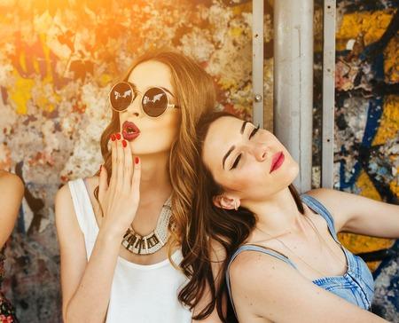 Dos hermosas chicas jóvenes descansan en una parada de autobús Foto de archivo