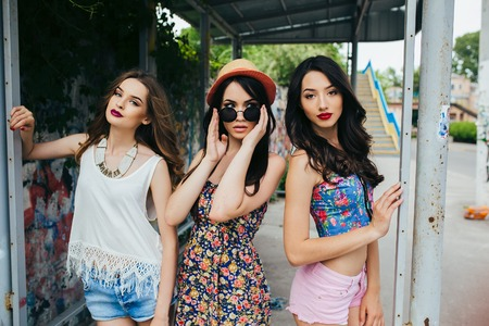 버스 정류장에서 포즈를 세 가지 아름 다운 젊은 여자