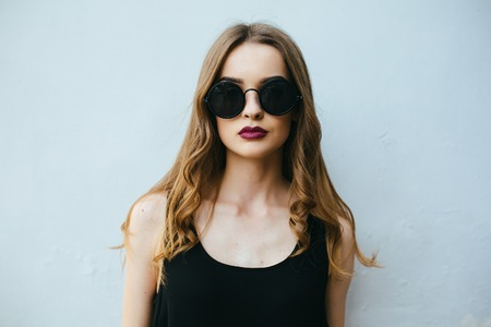 Attractive fashion woman in black dress with sunglasses posing near white wall Reklamní fotografie - 42826268
