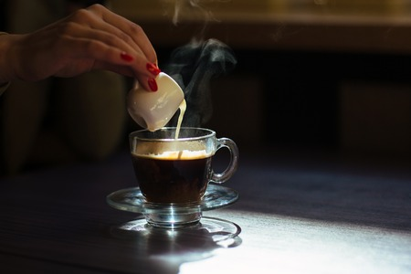 mleko: Morning cup of hot coffee with cream on table