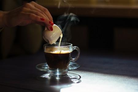 leche: Taza de la ma�ana de caf� caliente con crema en la mesa