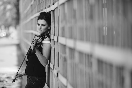 solo violinist: girl posing with violin in hand near the wall
