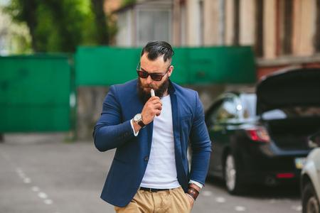 electronics: stylish well dressed man smoking electronic cigarette