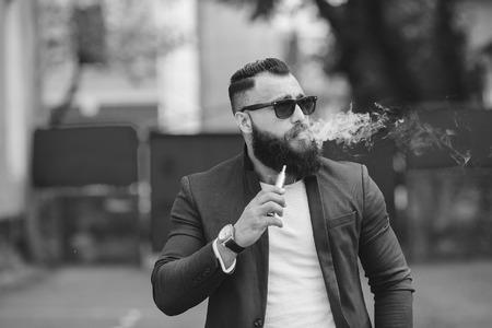 elegante hombre bien vestido fuma el cigarrillo electrónico Foto de archivo