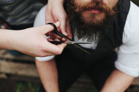 barber shave: barber shaves a bearded man in vintage atmosphere Stock Photo