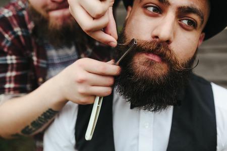 barbero afeita a un hombre barbudo en la atmósfera de la vendimia Foto de archivo