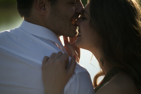 man woman kissing: beautiful couple on nature by the lake on the pier Stock Photo