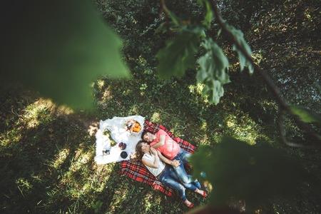 Foto hermosa pareja debajo de un árbol sobre un fondo de hierba Foto de archivo