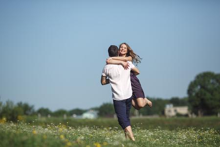 women hugging: beautiful couple runs across the field and fun