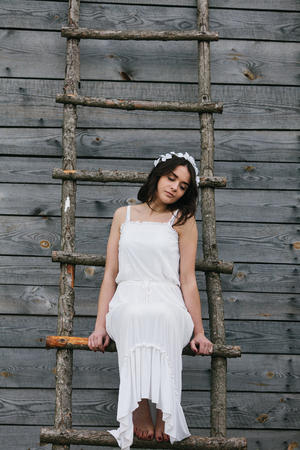 A girl sits on a wooden ladder and looking up