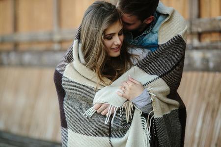 femme romantique: Jeune couple dans l'amour envelopp�e dans plaid debout et en regardant les uns les autres