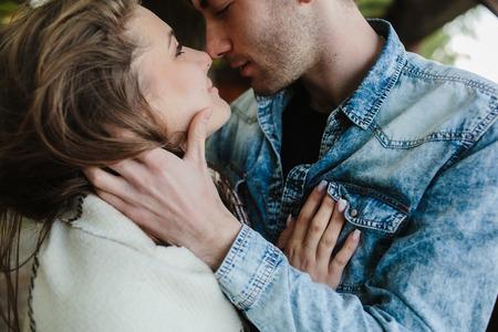 novios besandose: Pareja joven en el amor envuelto en tela escocesa de pie y mirando el uno al otro Foto de archivo