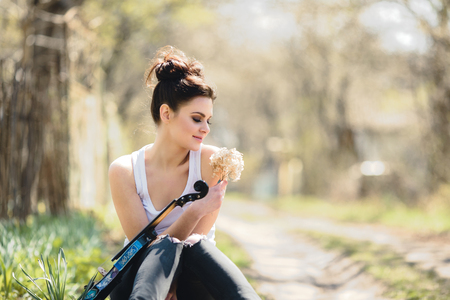 fiddlestick: beautiful girl with a violin in his hands posing sitting on the grass in the park