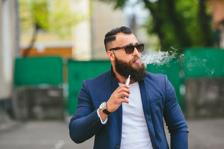 electronics: well dressed man with a beard smoking electronic cigarette