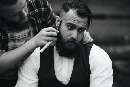 빈티지 분위기에서 수염을 가진 남자를 면도하는 이발사