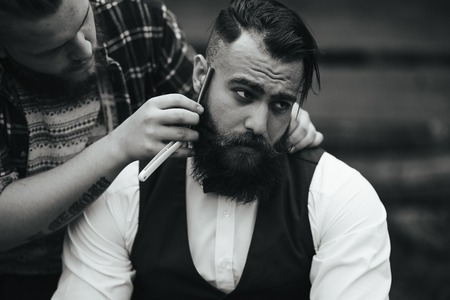 barber shaves a bearded man in vintage atmosphere Banco de Imagens
