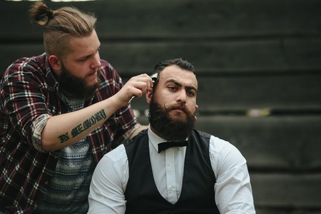 barbero: barbero afeita a un hombre barbudo en la atm�sfera de la vendimia Foto de archivo