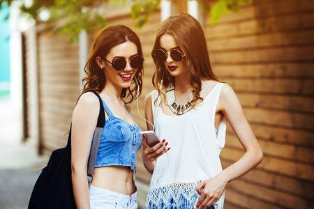 Twee jonge mooie meisjes lopen door de stad en luisteren naar muziek