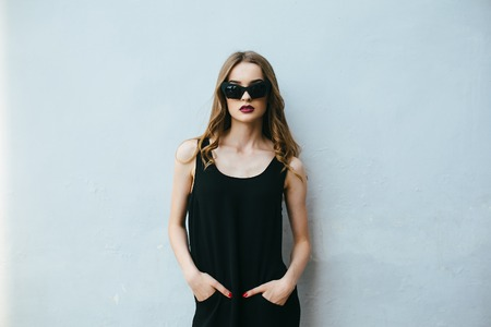 Attractive fashion woman in black dress with sunglasses posing near white wall