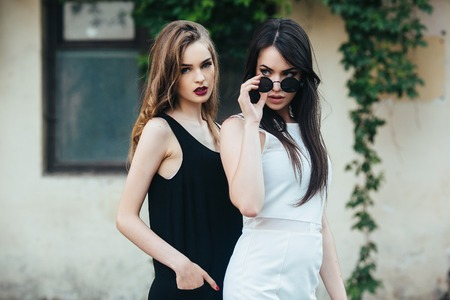 Two beautiful young girls in dresses posing in front of house