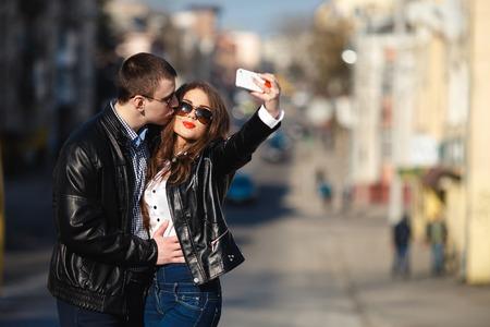 pretty teenage girl: beautiful couple making Selfe on a city street