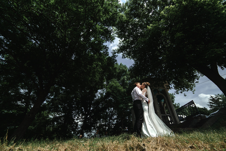 beautiful bride and groom run to each other on the background of the park