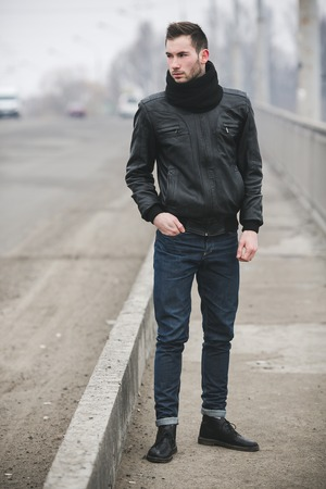 british ethnicity: A man dressed in jeans and jacket stands near the main road